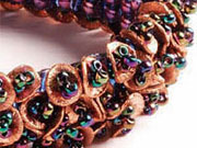A square stitch foundation with beaded fringe made of copper discs and amethyst seed beads