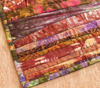 Learn how to sew a table runner using many techniques, such as this design using piecing.